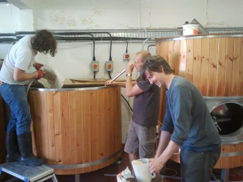 Tom scooping oats, Greg and Stu mash in...